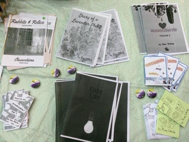 photo of a table covered with black and white zines and badges