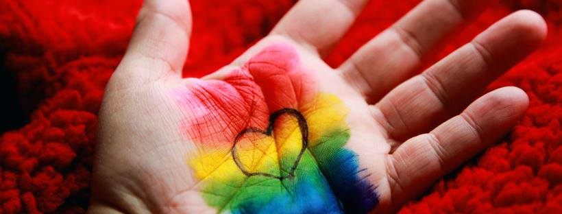 photo of a hand with rainbow paint and a heart on the palm