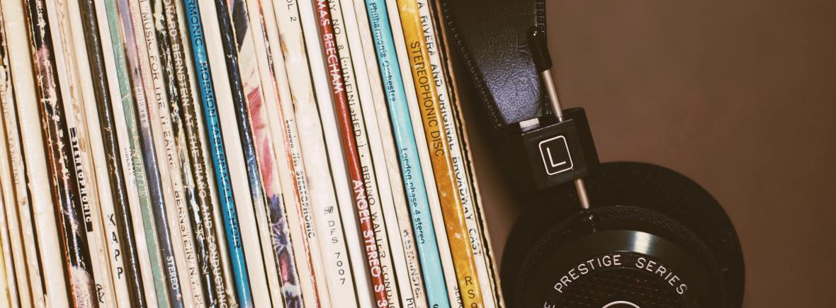 Vinyl stacked on a shelf beside black headphones