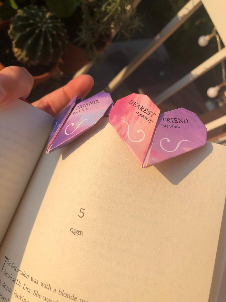 Photo of a two pink-purple origami heart-shaped bookmarks titled 'Dearest Friend, a poem by Rae White', attached to a page of a book, being held by a hand.