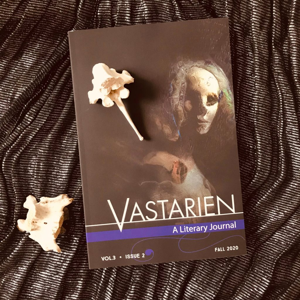Photo of a dark covered journal with a creepy wooden looking face on the front titled 'Vastarien A Literary Journal - Vol 3 Issue 2 - Fall 2020'. The journal sits on a black glitter cloth background with two horse spine bones as decoration.