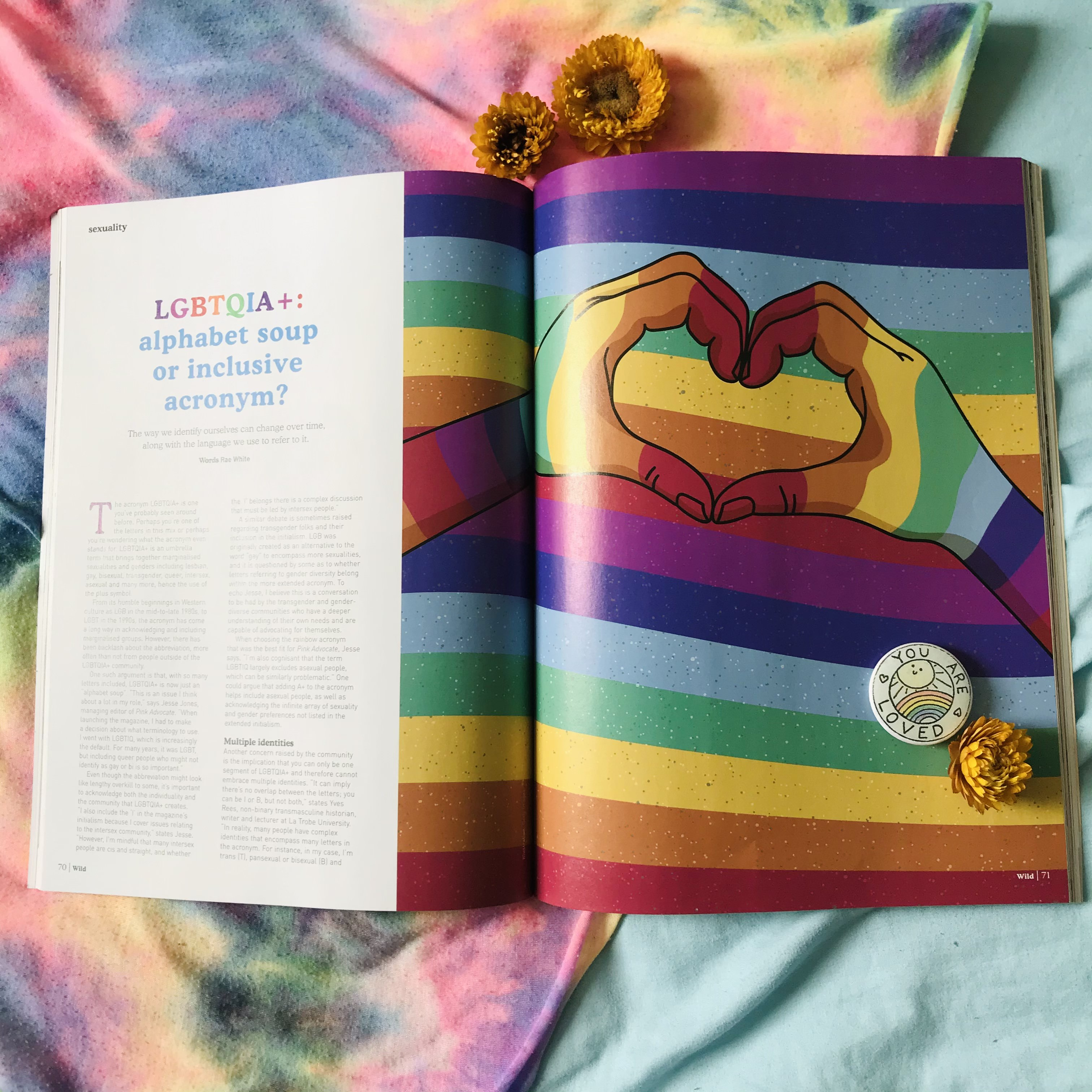 Photo of a magazine spread with the text 'LGBTQIA+: alphabet soup or inclusive acronym?' and a rainbow artistic image of hands in a heart shape, sitting on a background of rainbow with flowers and a 'you are loved' badge.