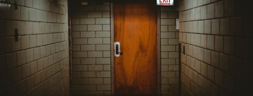 Photo of an orange door in a dimly lit, spooky-looking tiled room, a glowing exit sign in the right hand corner.