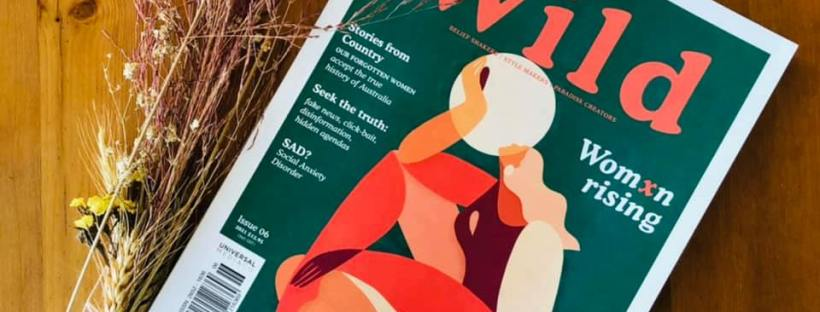 Photo of the front cover of Wild magazine, themed green and orange, with sprigs of flowers laid beside it.