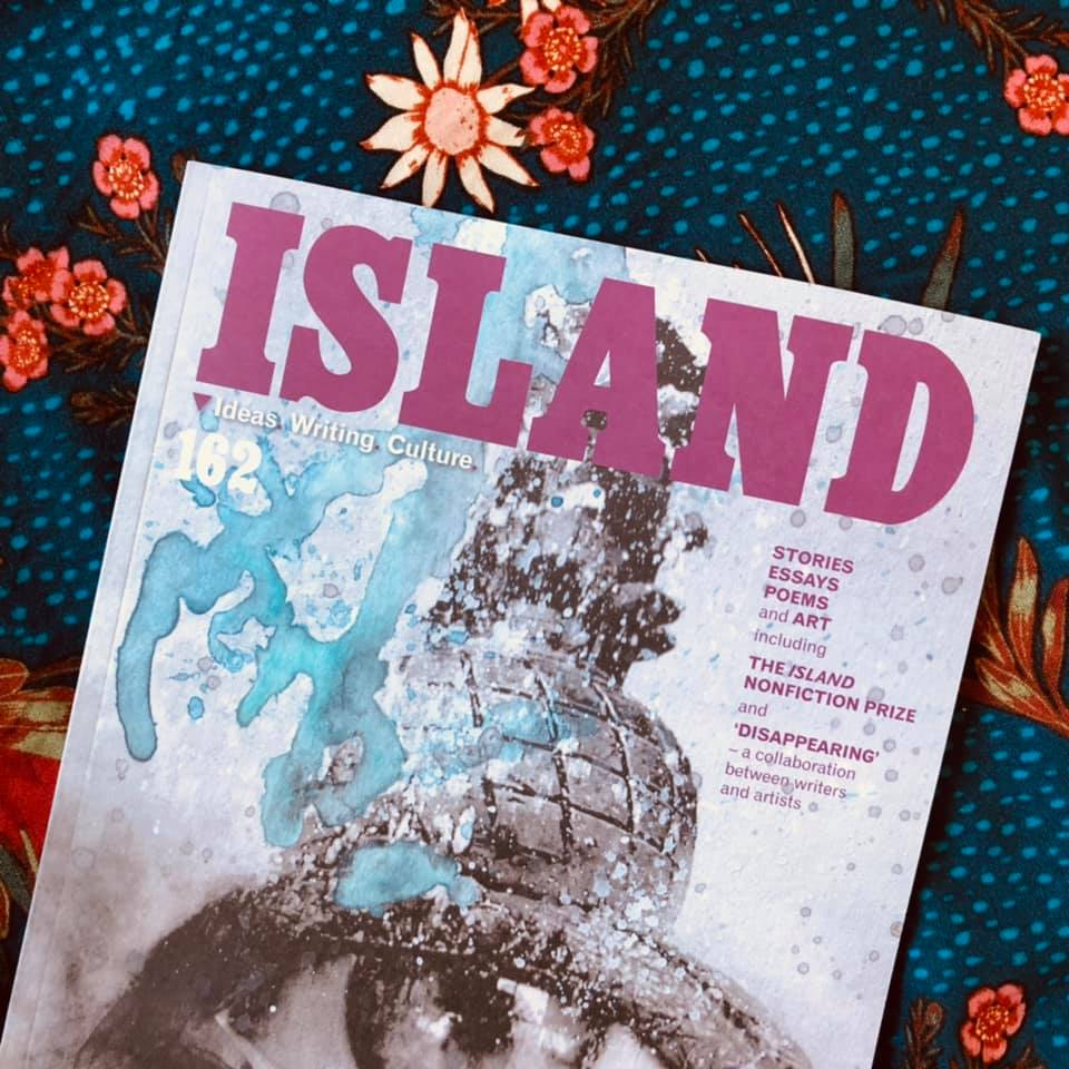 Photo of a magazine cover called Island with pink writing and the grey sketch of an eye, resting on a blue floral background.